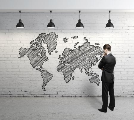 företag: man tittar på världskartan på tegelvägg Stockfoto