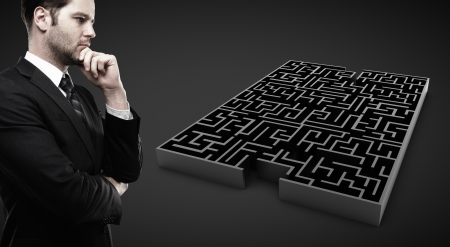 intricacy: man looking at black labyrinth  on black background Stock Photo