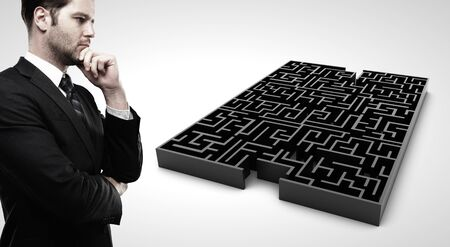 businessman looking at black labyrinth  on white background photo