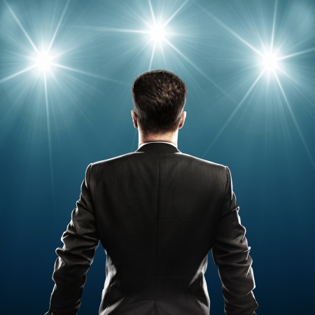 stage spotlight: businessman with suit, rear view