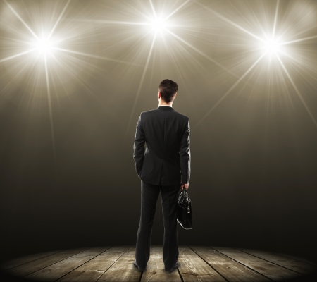 spotlight on stage: man with briefcase and lamp with with rays Stock Photo