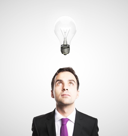 businessman looking at lamp on white background photo