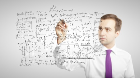 man drawing mathematical formulas on a board photo