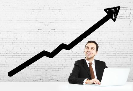 man sitting at table and graph of growth photo