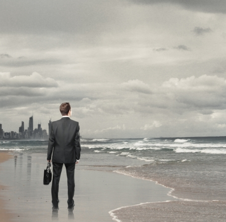dreams of city: Businessman standing on a beach Stock Photo