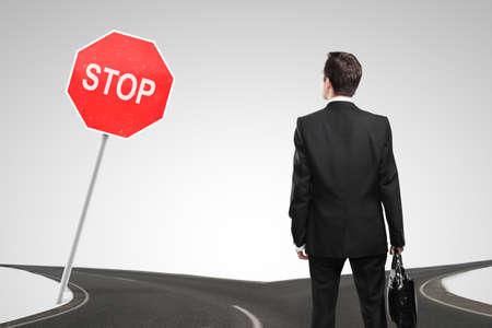 Uomo d'affari guardando un segnale di stop e crocevia