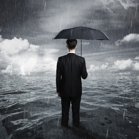 storm sea: man with umbrella business concept Stock Photo