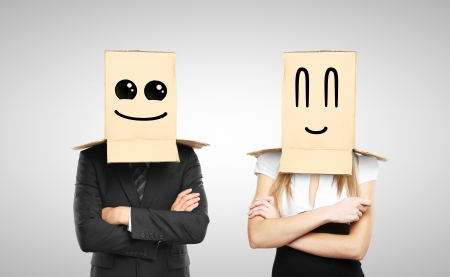 shyness: businessman and woman with smiling box on head Stock Photo