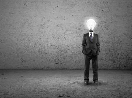 male costume: businessman with lamp-head on a concrete room Stock Photo