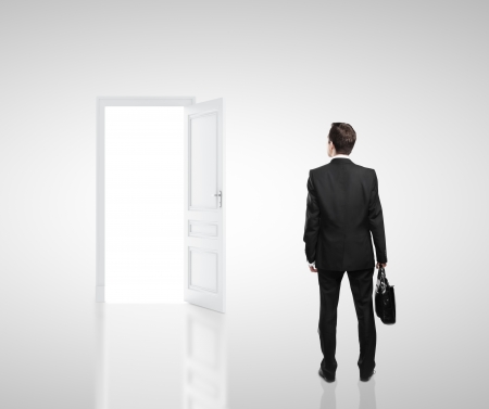 opening door: businessman in white room with doors open