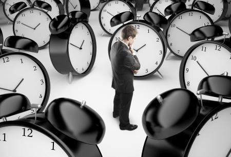 beat the clock: thoughtful businessman and alarm clocks Stock Photo
