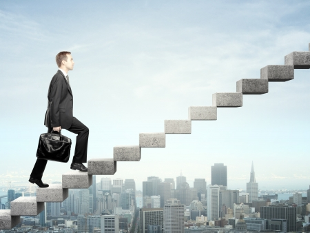 career development: Businessman stepping up a staircase and city