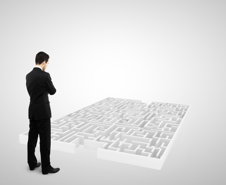 businessman standing and looking to white labyrinth photo