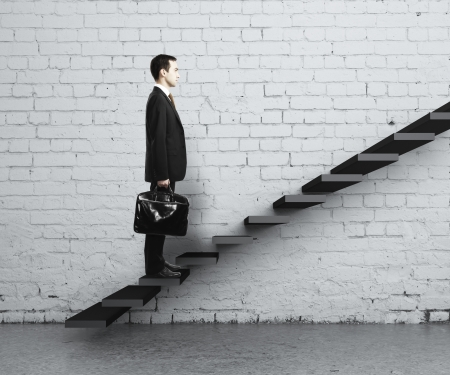 difficult journey: man stepping up a staircase Stock Photo