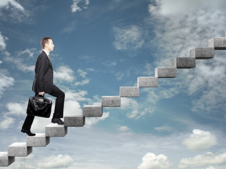 Businessman stepping up a staircase and sky photo