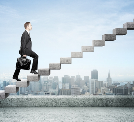 difficult journey: Businessman stepping up a staircase and city