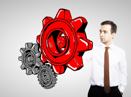 man drawing red gears on white background photo