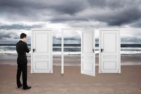 doors open: businessman standing on beach and opened doors