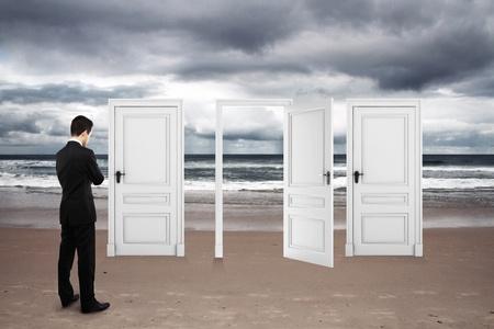 cielos abiertos: hombre de negocios de pie en la playa y las puertas abiertas Foto de archivo
