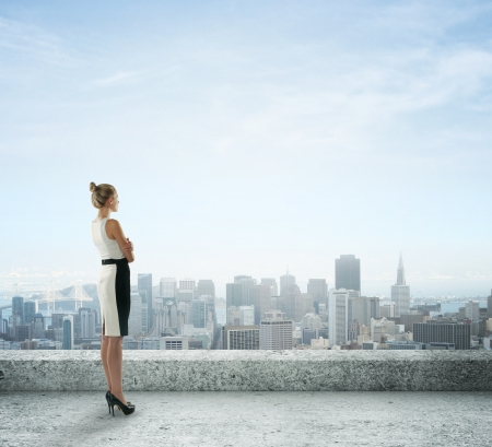 women business: businesswoman on roof looking at city