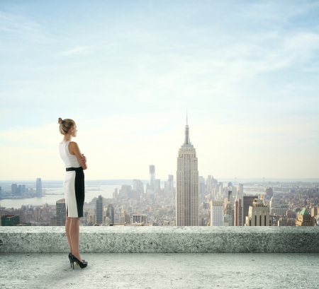 woman on roof looking at city photo