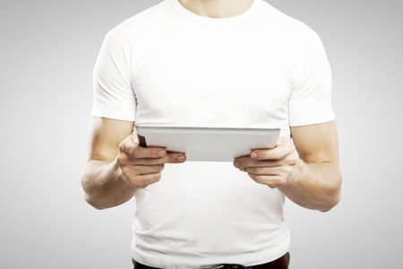 man in white t shirt holding touch pad
