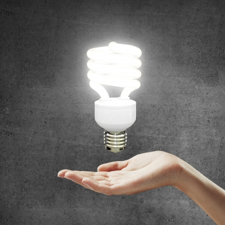 power point: hand and energy saving lamp on gray background