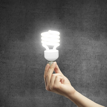 hand and energy saving lamp on gray background Stock Photo - 17689485