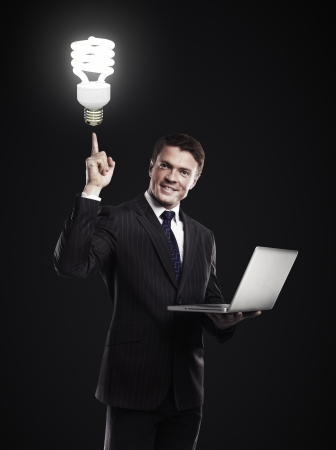 man with notebook pointing to energy-saving lamp Stock Photo - 17641245