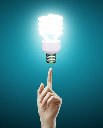 hand pointing to energy saving lamp photo