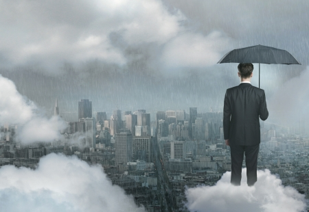 mbusinessman an on cloud with umbrella against background of city photo
