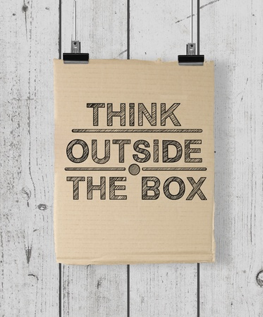 poster with think outside the box on a wood wall photo