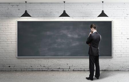 businessman looking at blackboard in loft interior photo