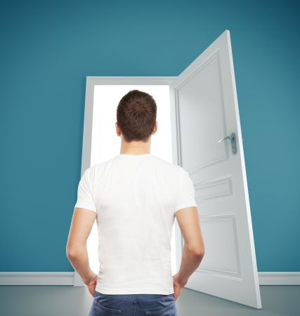 leaving: guy in T-shirt looking at  opened door Stock Photo