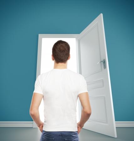 door man: guy in T-shirt looking at  opened door Stock Photo