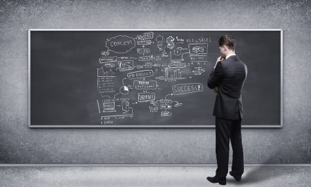 man looking at business strategy on blackboard Stock Photo - 17792914