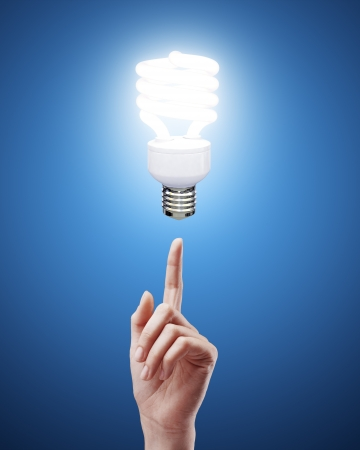 hand pointing to energy saving lamp on blue background Stock Photo - 17883409