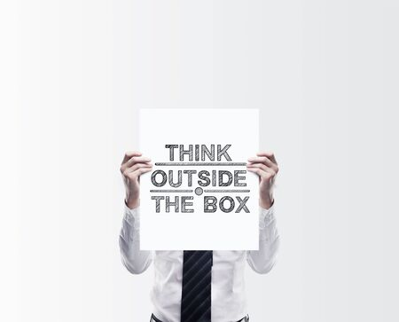 outside the box: businessman holding poster with think outside the box