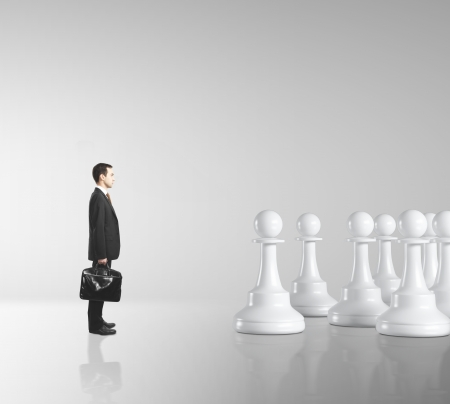 businessman and pawns on gray background