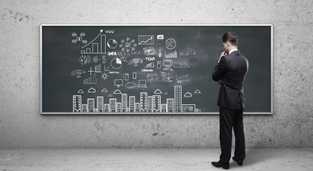 man looking at business strategy on blackboard photo