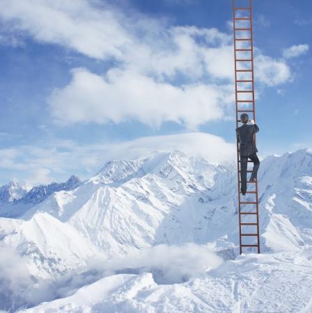 escaleras: hombre que sube en la escalera y las montañas Foto de archivo