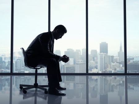 businessman sitting in office and city views in window