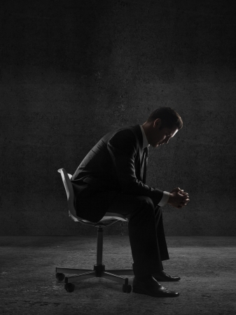 businessman sitting in a chair in concrete room photo