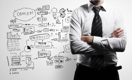 leadership: man in suit and business plan on wall Stock Photo
