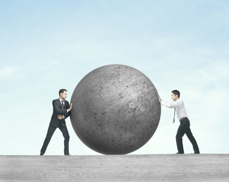 push up: two businessman pushing concret ball