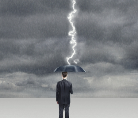argent: Businessman with umbrella in thunderstorm