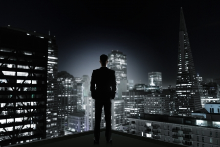 city by night: man in office looking to night city