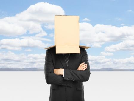 shyness: businessman with a box on head and blue sky