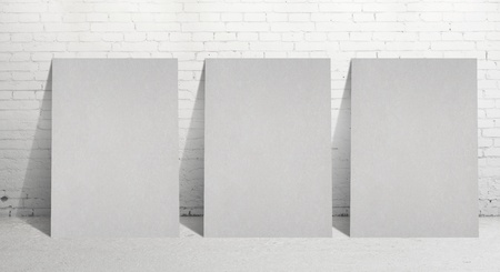 three paper poster and  brick wall photo