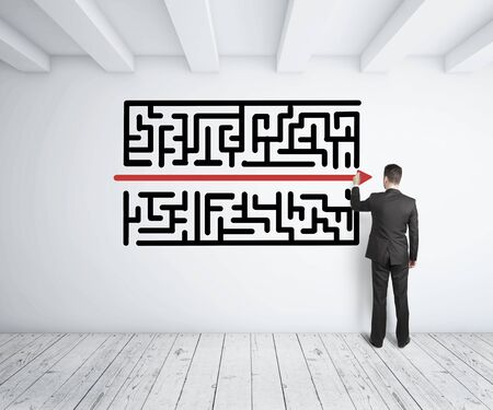 and simplicity: businessman drawing maze on white wall